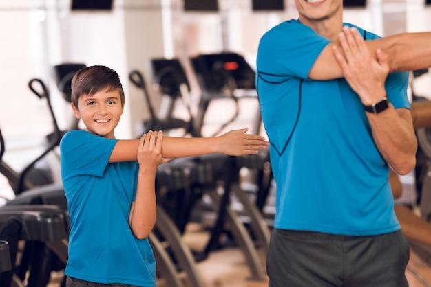 Papá e hijo hacen ejercicios de calentamiento en el gimnasio.