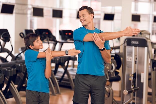 Papá e hijo hacen estiramientos en el gimnasio.