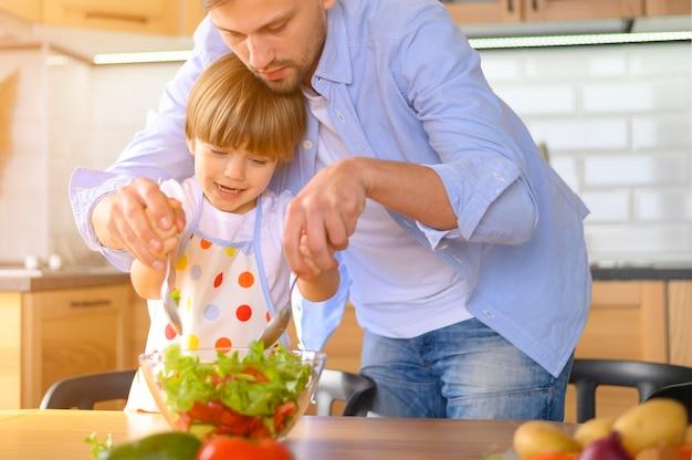 Papá e hijo haciendo una ensalada