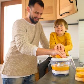 Papá e hijo haciendo jugo de naranja