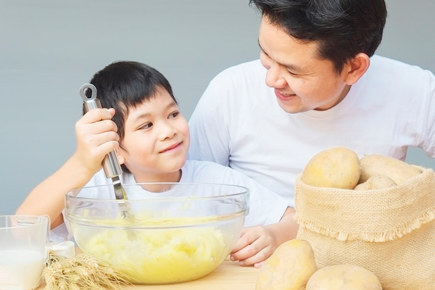 Papá e hijo haciendo puré de papas alegremente
