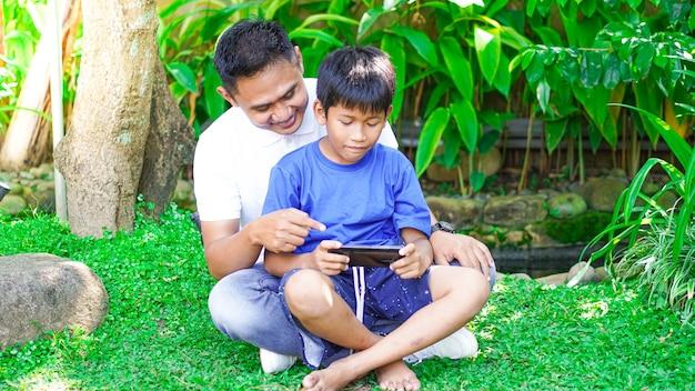 Papá e hijo juegan juegos móviles en el parque.