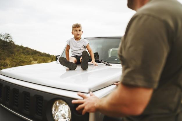 Papá e hijo jugando en el capó de un coche en viaje por carretera