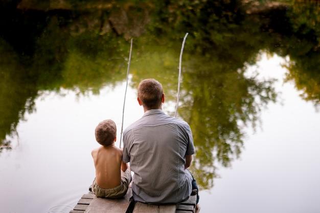 Papá e hijo pescando en un lago