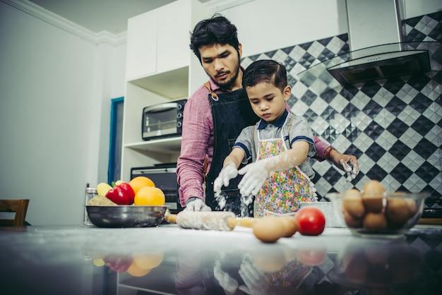 Papá enseña a su hijo a cocinar en la cocina en casa. concepto de familia