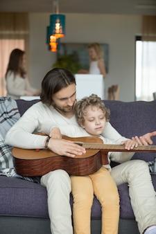 Papá enseñando a su pequeño hijo a tocar la guitarra, hija cocinando ayudando a la madre