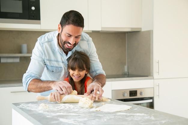 Papá feliz y alegre y su niña disfrutando del tiempo juntos mientras amasan y amasan la masa en la cocina.