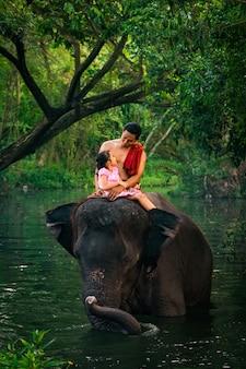 Papá feliz e hija sentada en el elefante, tailandia