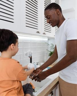 Papá feliz lavando platos junto a su hijo