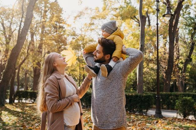 Papá feliz y mamá con bebé al aire libre