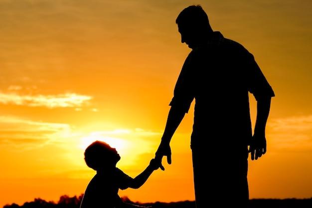 Papá feliz con un niño en la silueta del parque al aire libre