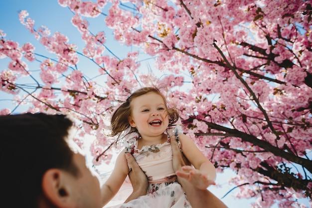 Papá feliz tiene hijita en sus brazos de pie bajo el árbol con flores