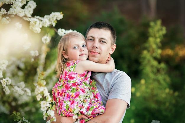 Papá en un floreciente jardín de cerezos sostiene en sus brazos a su amada hijita linda de 3 años