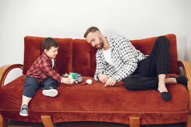 Papá guapo con niño en el sofá