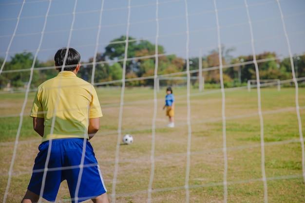 Papá guapo con su pequeño se divierte y juega al fútbol en césped verde