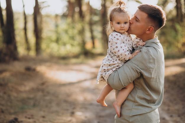 Papá con hija pequeña abrazándose en el bosque