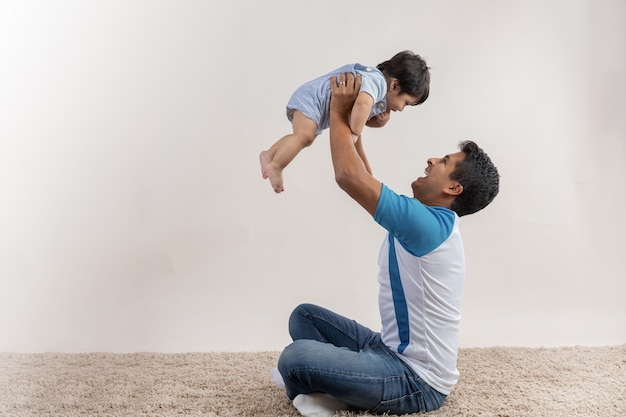 Papá con hijo en el aire con los brazos extendidos el día del padre