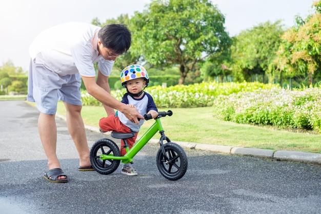 Papá, hijo tecnológico para montar bicicleta de equilibrio