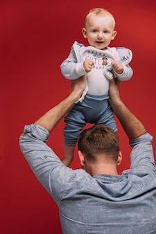 Papá irreconocible sosteniendo a su lindo hijo en brazos por encima de su cabeza sobre fondo rojo. niño sonriente mirando a la cámara.