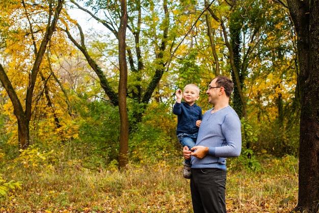 Papá joven con un hijo pequeño sosteniendo mirando hacia arriba y caminando en el parque de otoño