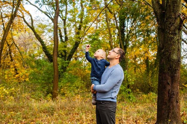 Papá joven con un hijo pequeño sosteniendo mirando a la castaña, caminando y estudiando la naturaleza
