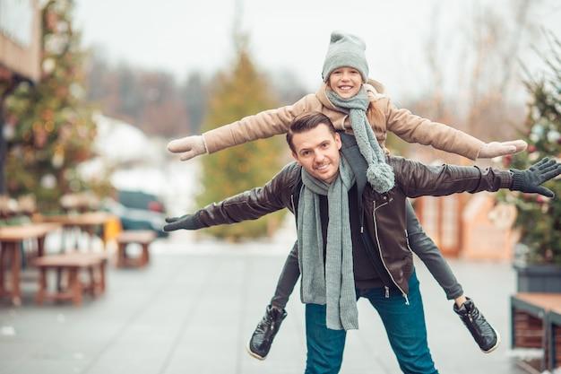 Papá joven y niña adorable se divierten en la pista de patinaje al aire libre