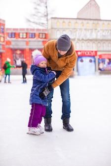 Papá joven y niña adorable se divierten en la pista de patinaje