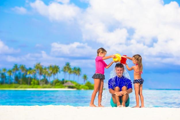 Papá joven y niñas divirtiéndose durante las vacaciones de verano en la playa