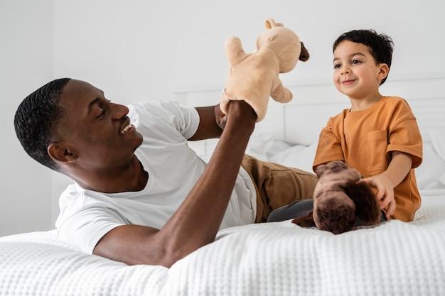 Papá joven pagando con juguetes con su hijo