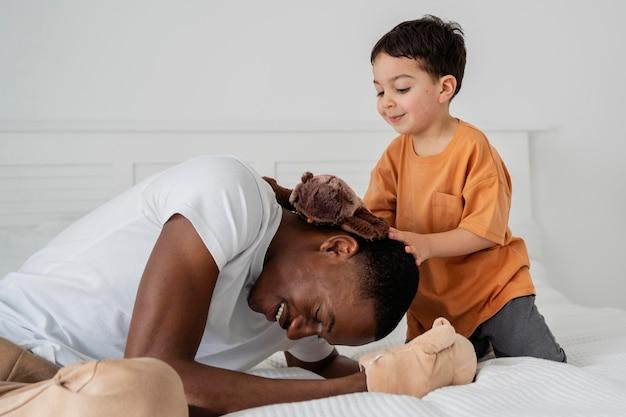 Papá joven riendo y pagando con su hijo