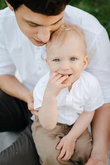 Papá joven sostiene a un niño pequeño feliz sentado en el césped en el parque un niño rubio mientras está sentado en los brazos de sus padres