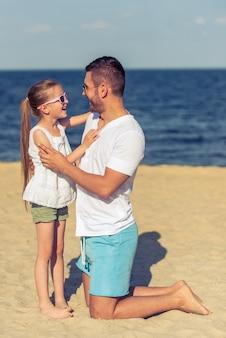 Papá joven y su pequeña hija linda en gafas de sol.