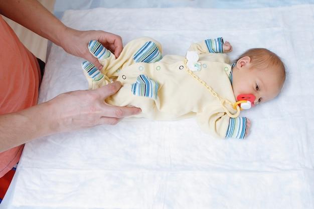 Papá juega con un bebé recién nacido en la cama. hija en mono de bebé con chupete. infancia feliz. cuidado de padres.