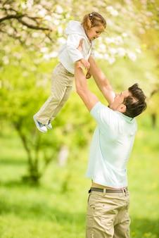 Papá está jugando con pequeña hija bonita en el parque de verano.