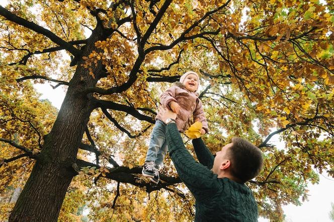 Papá levantando a su hija sonriente en el bosque de otoño