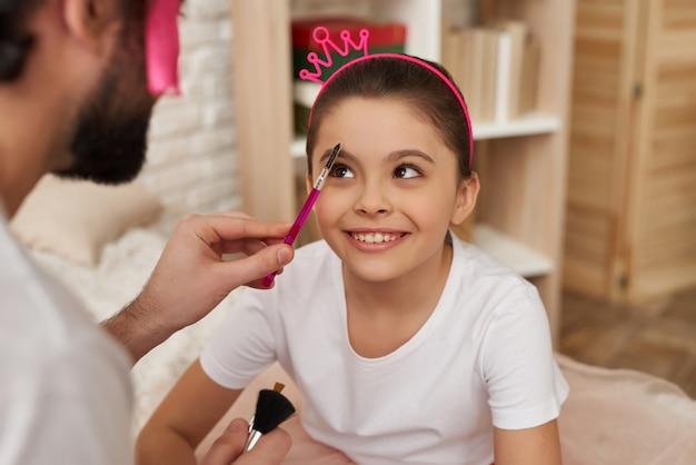 Papá limpia la cara de las pequeñas hijas con un cepillo.