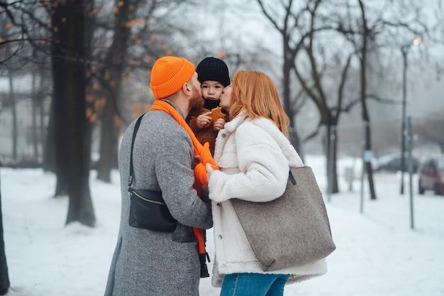 Papá mamá y bebé en el parque en invierno