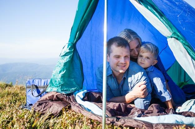 Papá, mamá e hijo mirando fuera de la carpa mientras viajan por las montañas