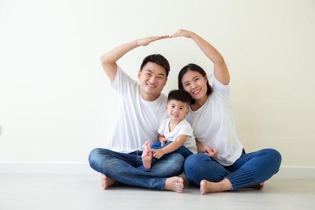 Papá y mamá haciendo techo figura hogar con las manos sobre la cabeza, familia asiática con hijo sentado en el piso de la habitación, nuevo edificio residencial compra concepto de apartamento