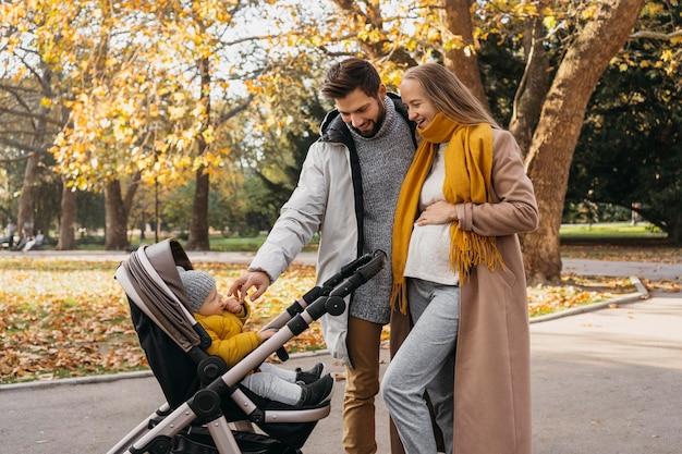 Papá y mamá con niño en cochecito al aire libre
