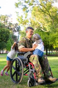 Papá militar discapacitado alegre caminando con dos niños en el parque. niña empujando las asas de la silla de ruedas, niño sentado en el regazo de los papás. veterano de guerra o concepto de discapacidad