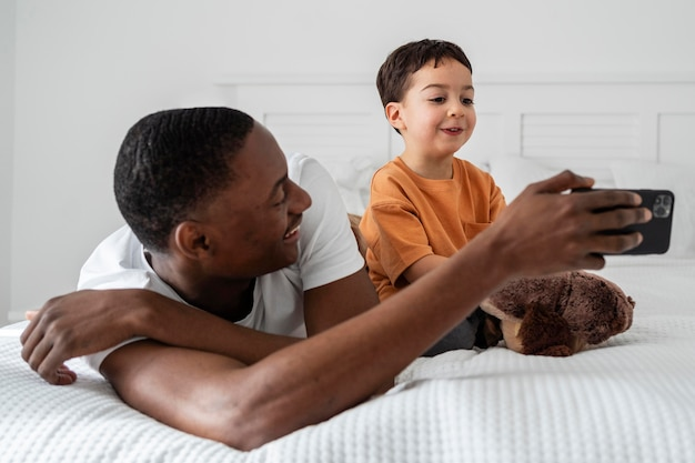Papá mostrando a su hijo algo en el teléfono