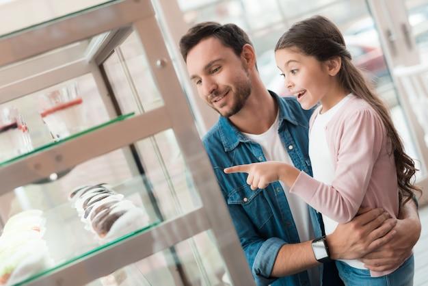 Papá y niña eligen sabrosos dulces en el café.