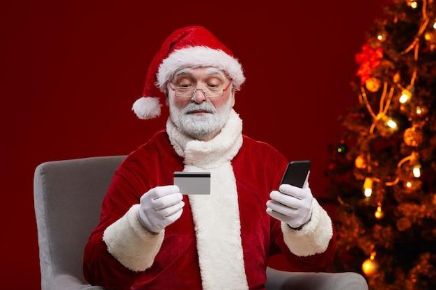 Papá noel barbudo en anteojos con tarjeta de crédito y pago en línea usando su teléfono móvil