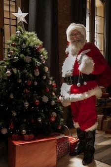 Papa noel con bolsa de regalos cerca del árbol de navidad