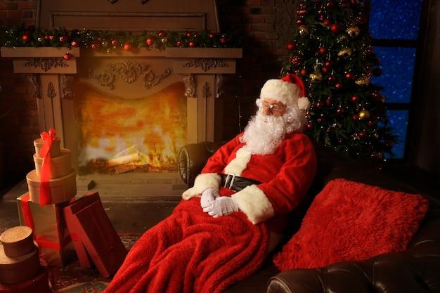 Papá noel descansando en una cómoda silla cerca de la chimenea en casa.