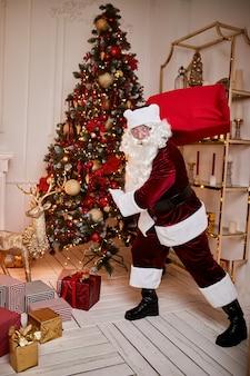 Papá noel con una gran bolsa roja de regalos se apresura a llevar presente a los niños. feliz navidad, felices fiestas concepto