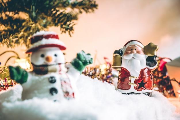 Papá noel y muñeco de nieve con adorno iluminación bombilla noche santa