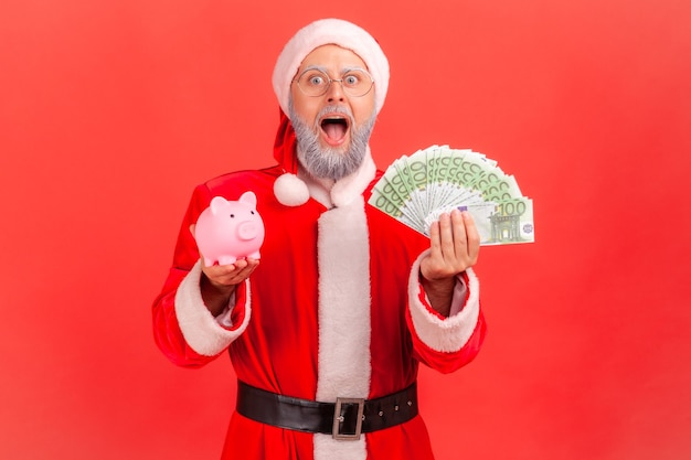 Papá noel de pie con billetes en euros y hucha, gran cantidad de dinero.