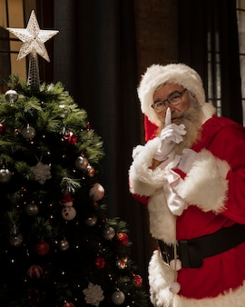 Papá noel posando junto al árbol de navidad
